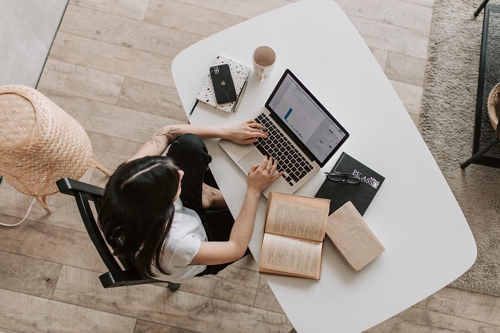 Vista de cima de um escritório. Mulher trabalhando em um notebook, com livros e cadernos ao lado.
