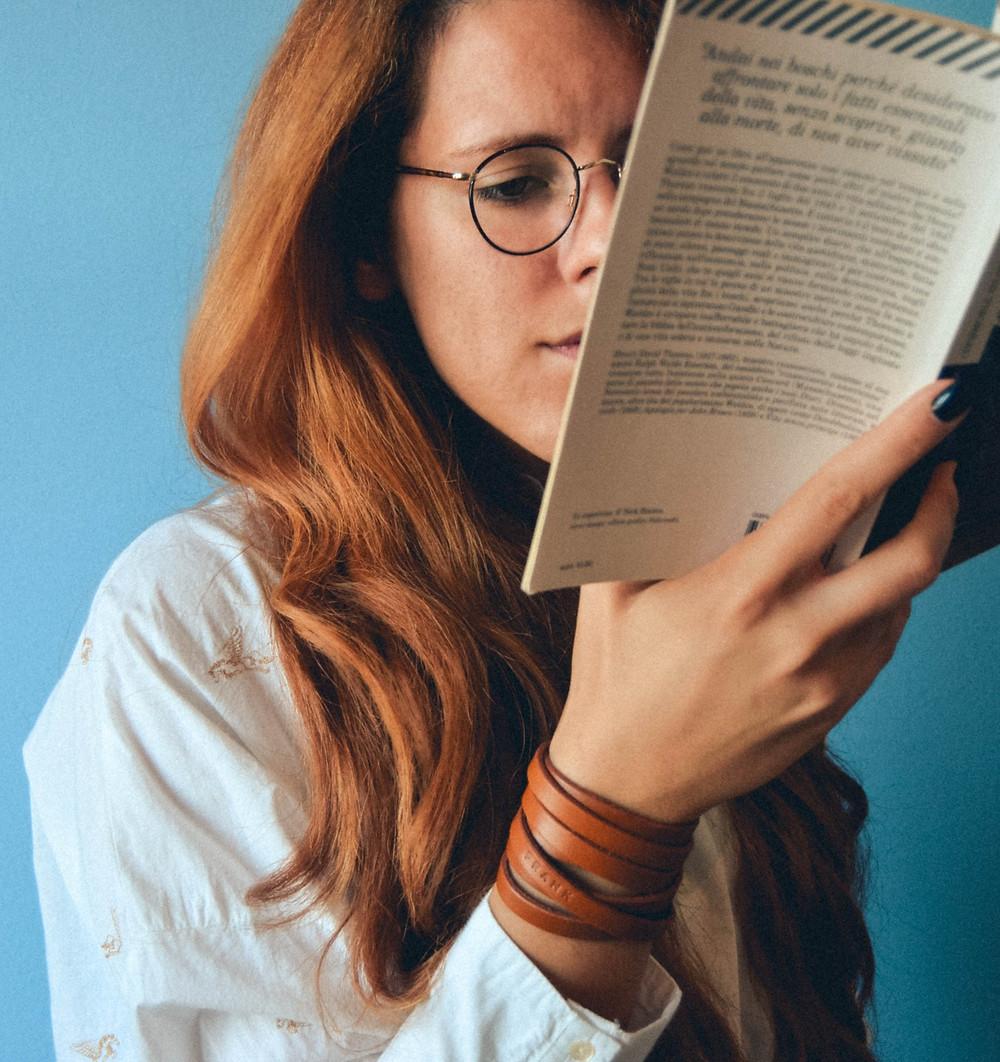 Parede ao fundo azul. Mulher ruiva usando óculos lê um livro que segura apenas com a mão direita. Ela veste camisa branca e uma pulseira de fita de couro.