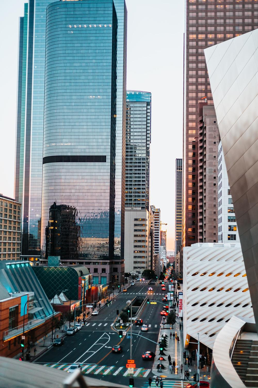 Rua movimentada no centro de uma cidade. Grandes prédios modernos e empresariais, construídos em vidros e espelhados, ladeiam a avenida.