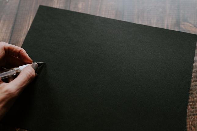 Imagem ilustrativa. Mão segurando uma caneta sobre uma folha de papel escura.