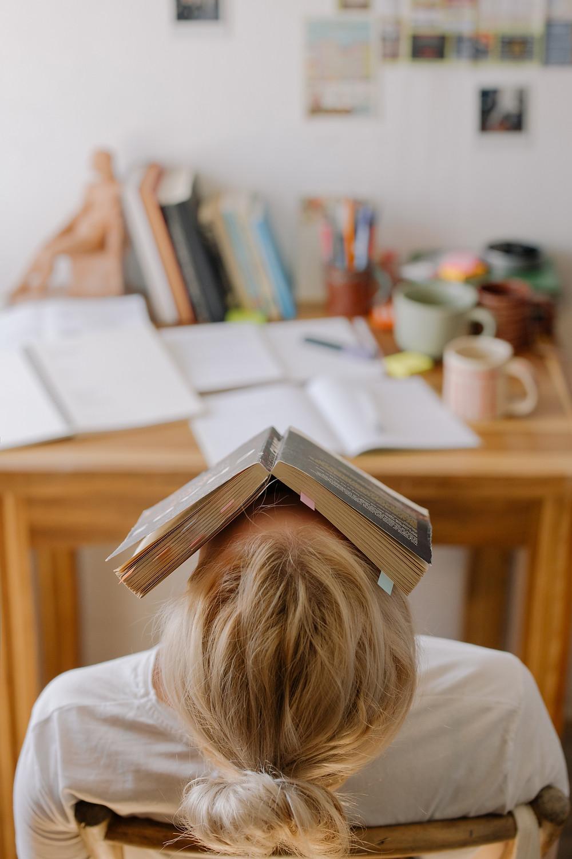 Pessoa com um livro sobre o rosto e a cabeça apoiada no encosto da cadeira, representando cansaço. Sobre a mesa, pilhas de papel, livros e anotações.