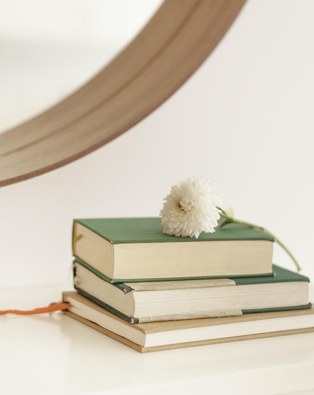 Pilha com três livros sobre uma mesa branca. Sobre os livros uma flor de cravo. Ao fundo o canto de um espelho.