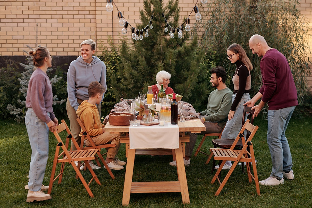 Família reunida ao redor de uma mesa de madeira no pátio com grama. Pessoas de todas as idades, umas em pé e outras sentadas, conversando entre si.