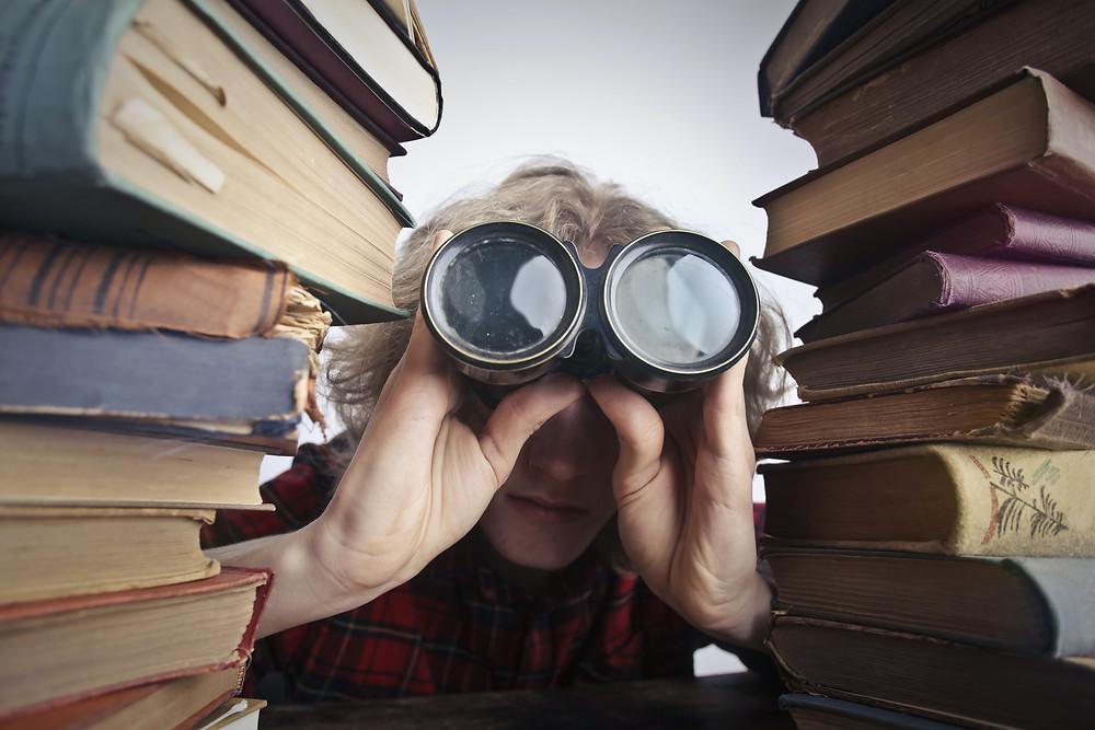 Duas pilhas de livros. Um homem entre elas olhando por um binóculos.