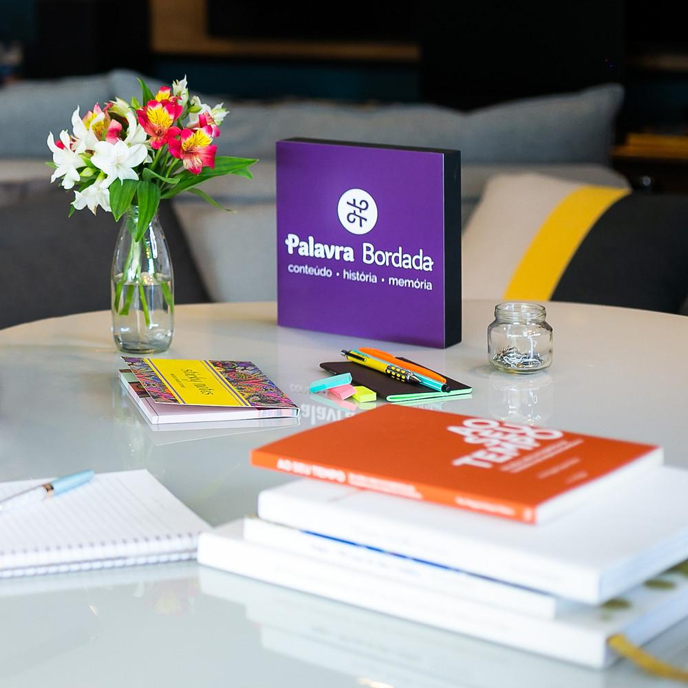 Livros da Palavra Bordada sobre uma mesa e ao lado de cadernos, canetas e um vaso de flor. Ao fundo a logo da editora.