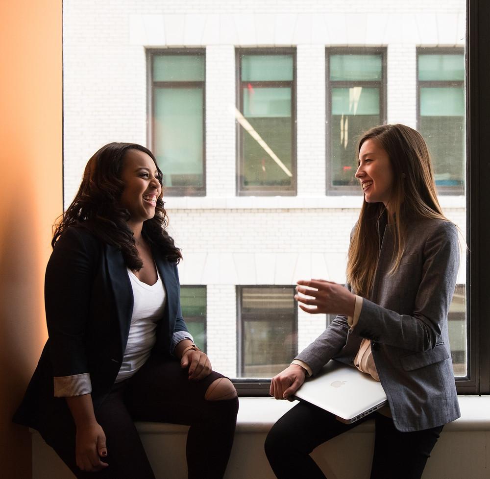Duas mulheres sentadas próximas de uma janela, lado a lado, olhando-se de frente, conversando e sorrindo. A mulher da esquerda segura um notebook. Ao fundo é possível ver as janelas de outro prédio.
