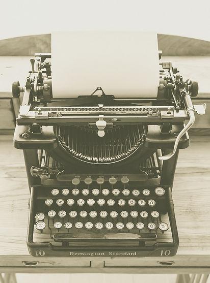 Imagem ilustrativa. Máquina de escrever com uma folha em branco.