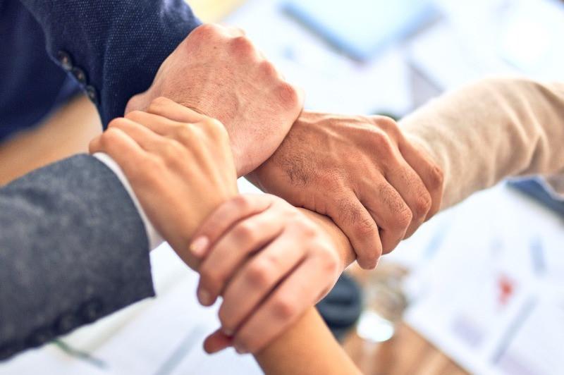 Imagem ilustrativa. Pessoas de mãos dadas, formando um quadrado com os braços, uns sobre os outros