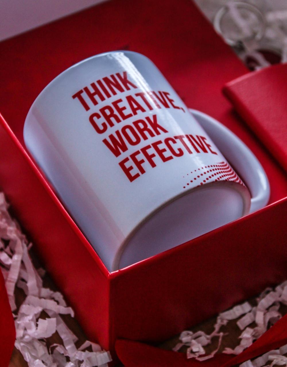 """Caneca branca, com a frase """"Think Creative, Work Effective"""", escrita em letras vermelhas maiúsculas. A caneca está em uma caixa vermelha, sobre um fundo de papeis."""