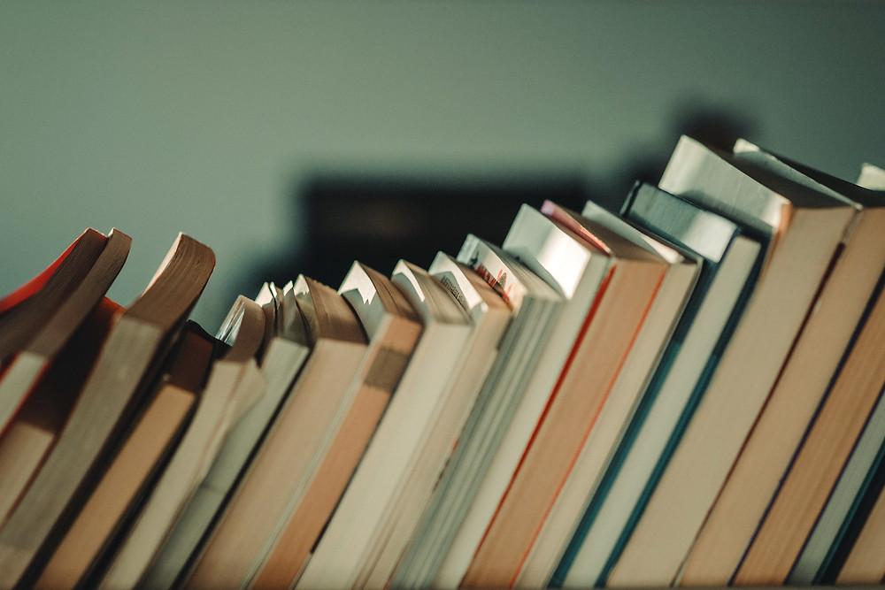 Fileira de livros organizados em pé sobre uma prateleira ou móvel, inclinados para a direita. Livros de diferentes tamanhos, de capa dura ou não.