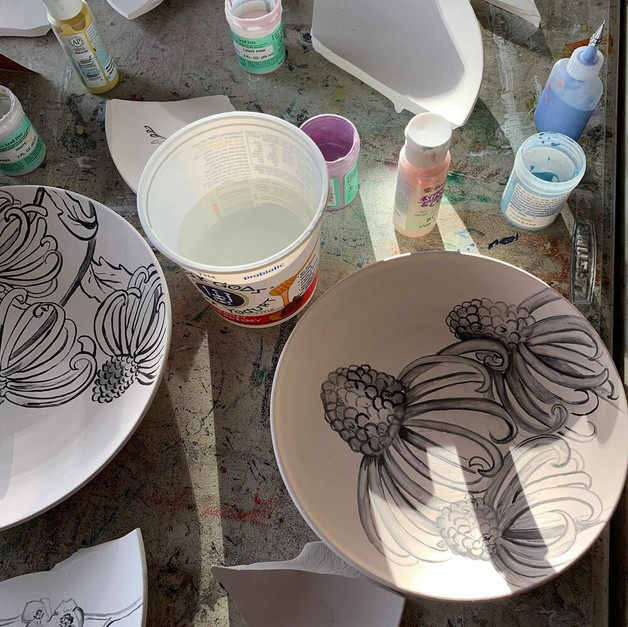 GLAZING WORKSHOP PREP: Before the workshop, the artist team used underglaze to paint images onto plates, both shattered and whole, that made up this installation. The image depicts Dolores, in her uniform, emerging from a field of wildflowers.