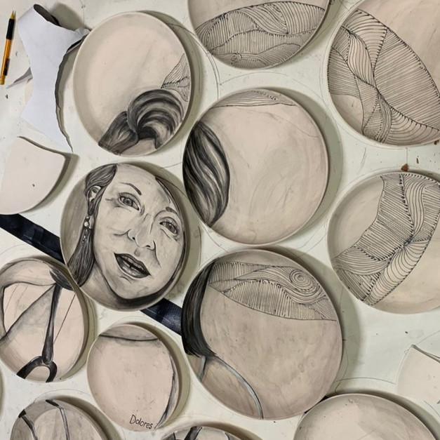 DOLORES IN PROGRESS: Before the workshop, the artist team used underglaze to paint images onto plates, both shattered and whole, that made up this installation. The image depicts Dolores, in her uniform, emerging from a field of wildflowers.