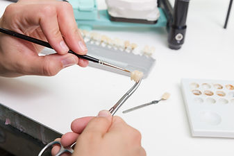 painting a tooth crown in dental laborat