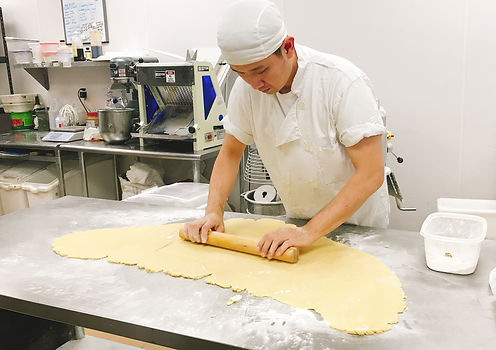 Mr. Yoon is rolling out the dough
