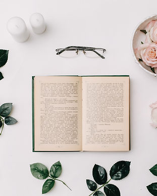 Opened book, glasses, pink roses on whit