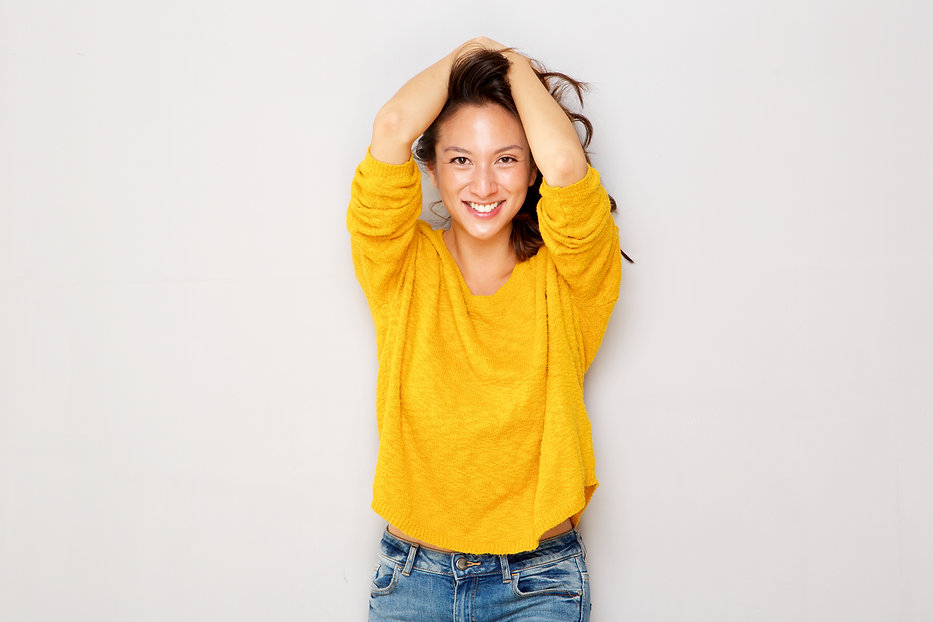 happy-asian-girl-smiling-with-hands-in-hair-3DVFS2N.jpg