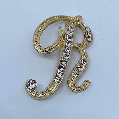 "Crystal studded gold ""R"" boutonnière"