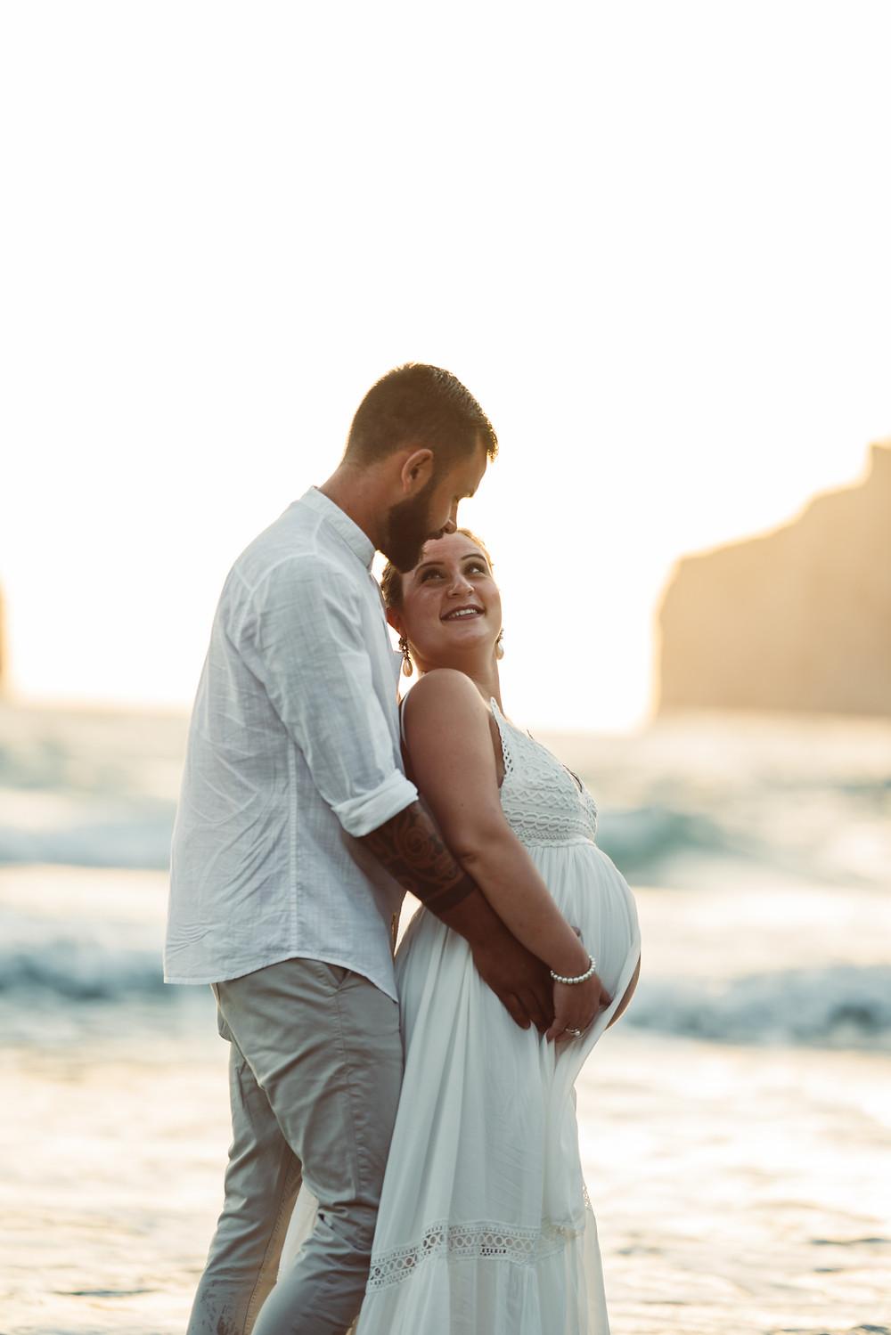 genitori si abbracciano in spiaggia a masua, fotografia gravidanza Sardegna