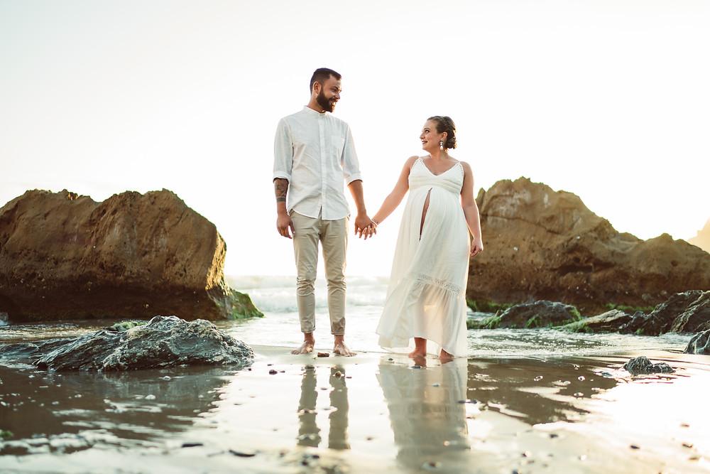 genitori si guardano in spiaggia a masua, fotografia gravidanza Sardegna
