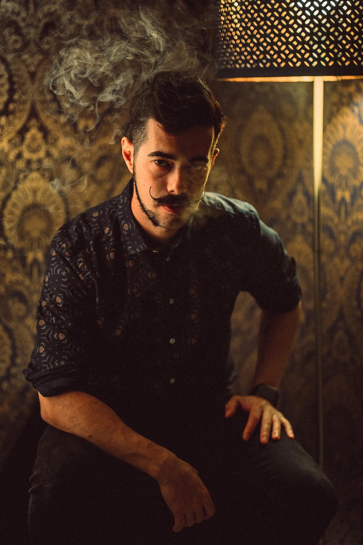 fotografia di ritratto artistico Iglesias, luce di taglio, sguardo diretto, fumo, sfondo damascato, luce di lampada nello sfondo
