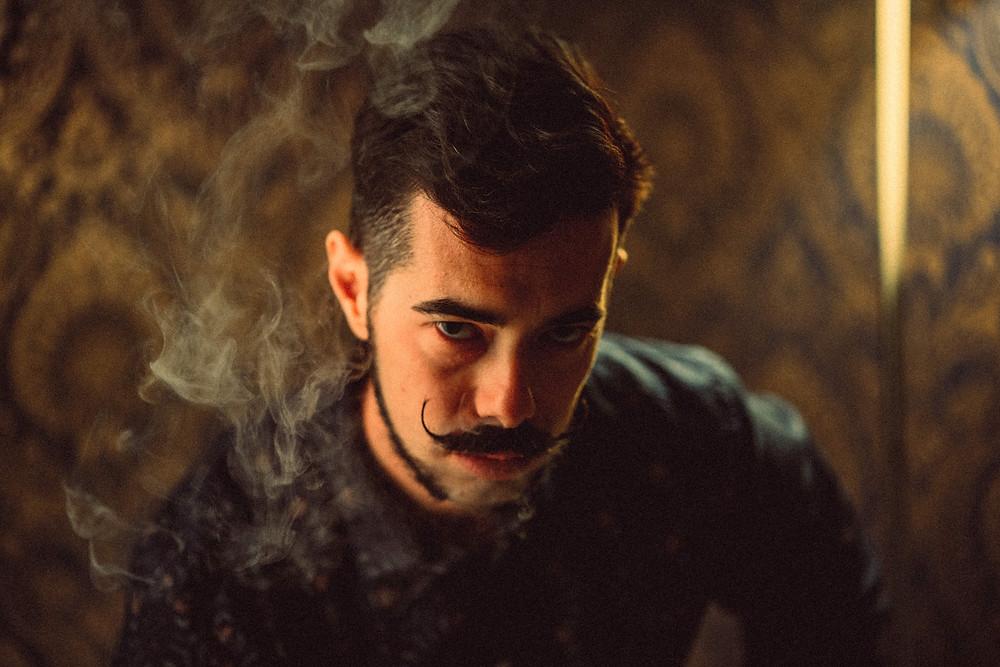 fotografia di ritratto artistico Iglesias, luci cinematografiche, stile film, luci calde, fumo