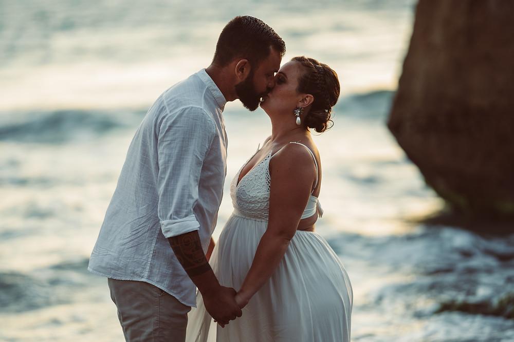genitori si baciano in spiaggia a masua, fotografia gravidanza Sardegna