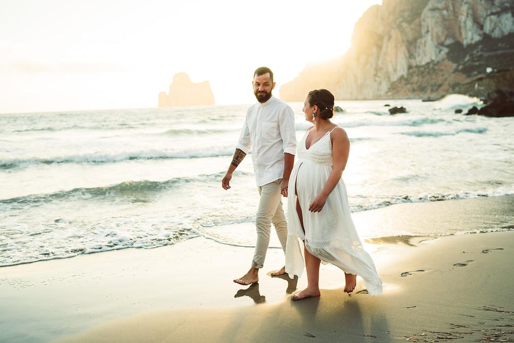 genitori passeggiano in spiaggia a masua, fotografia gravidanza Sardegna