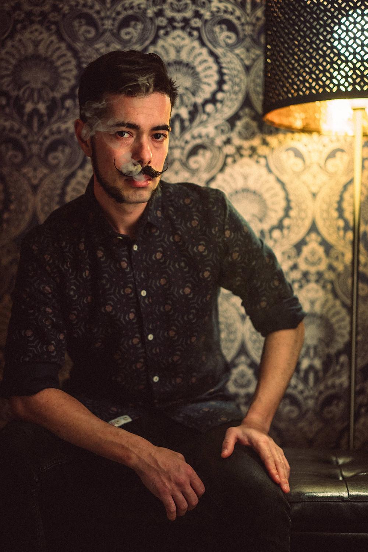 fotografia di ritratto artistico Iglesias, sguardo diretto, fumo fuoriesce dalla bocca