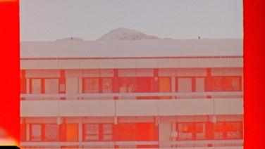 NUTSIGASSAT   (idem)  Tinne Zenner, Groelândia, 2018, 20 min.  Enquanto os blocos habitacionais carregam um passado de diáspora nacional, camadas de neve cobrem um desenvolvimento futuro na cidade de Nuuk, Groenlândia. A paisagem funciona como um cenário por nostalgia coletiva e produção industrial, como o filme estuda falhas na tradução da linguagem e da cultura em uma modernidade pós-colonial.  DATAS E HORÁRIOS DE EXIBIÇÃO - CINEMATECA DO MAM 15/07 - 17H10 17/07 - 18H20