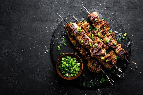 Grilled meat skewers, shish kebab on bla