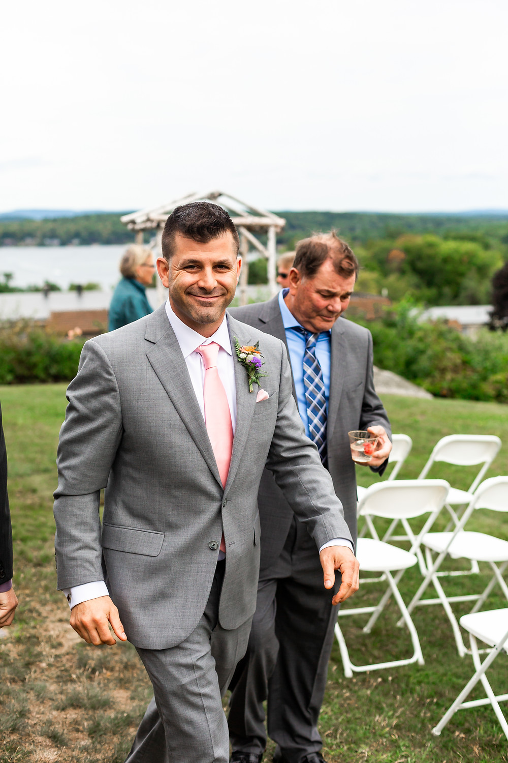 The groom walks across the lawn at the grandview resort in Laconia New Hampshire on his wedding day.