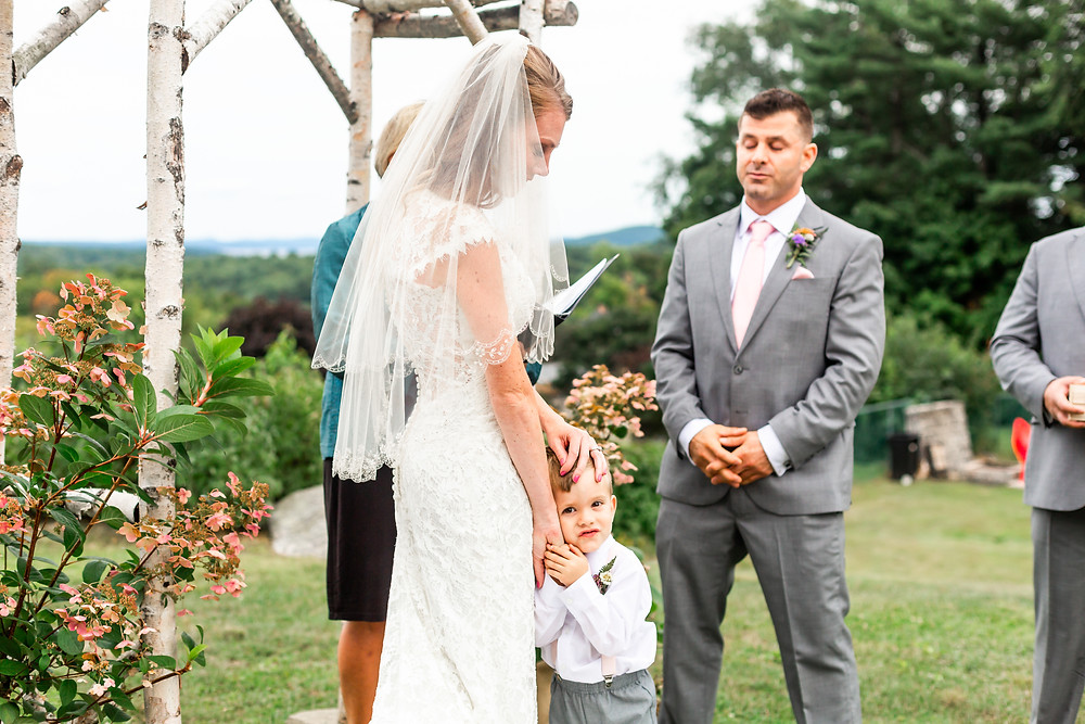 Maine Elopement and intimate wedding photographer captures tender moment between mom and son at outdoor wedding.