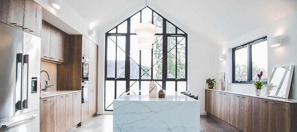 Open plan kitchen with a slab door in a dark woodgrain colour.