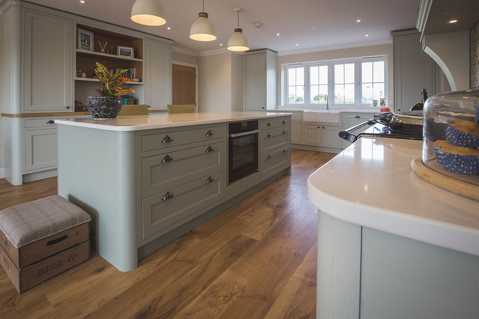 A light green in-frame kitchen.