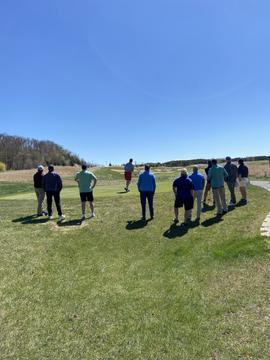Golfers watching tee off