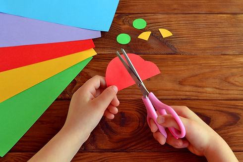 Child cuts a car out of paper. Sheets of colored paper. Kids art. Kids crafts. Crafts concept.jpg