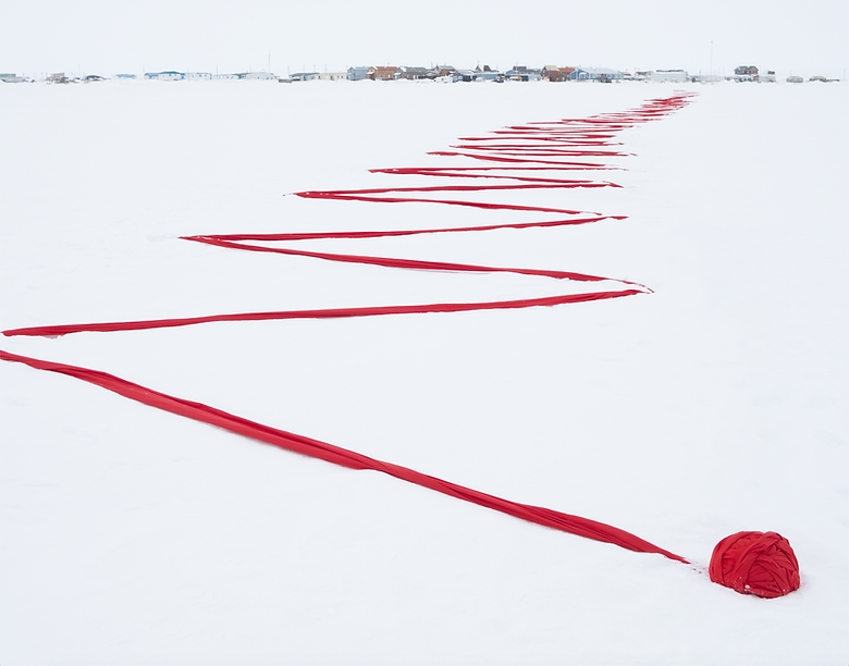 Ball of red cloth leading into red cloth zigzag across snow. The zigzag goes back vertically