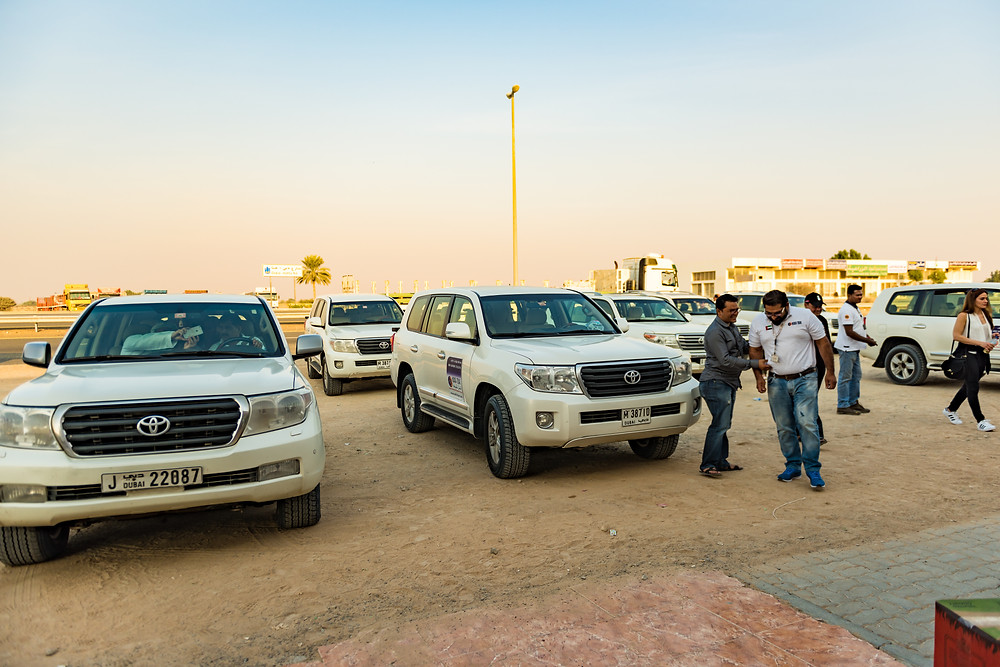 Desert safari drivers shoot the shit while they wait on their customers\