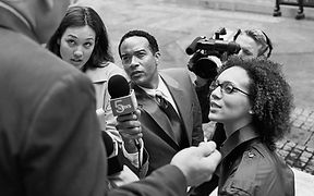 An image of reporters confronting a lawyer on the courthouse steps.