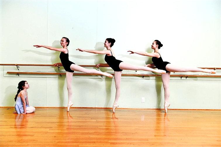 Little girl admiring older ballet dancers