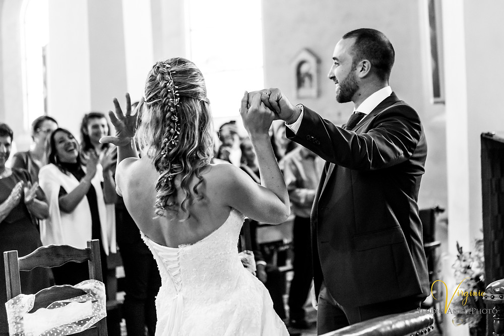 les mariés montrent leurs mains avec leurs alliances aux invités à l'église