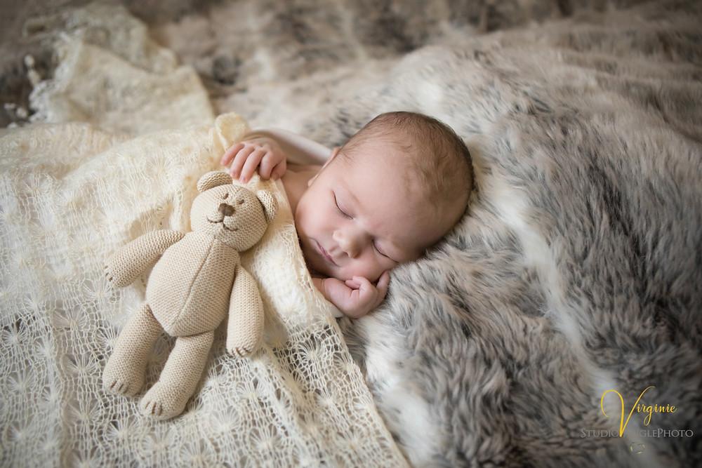 nouveau né avec son doudou sur un plaid tout doux