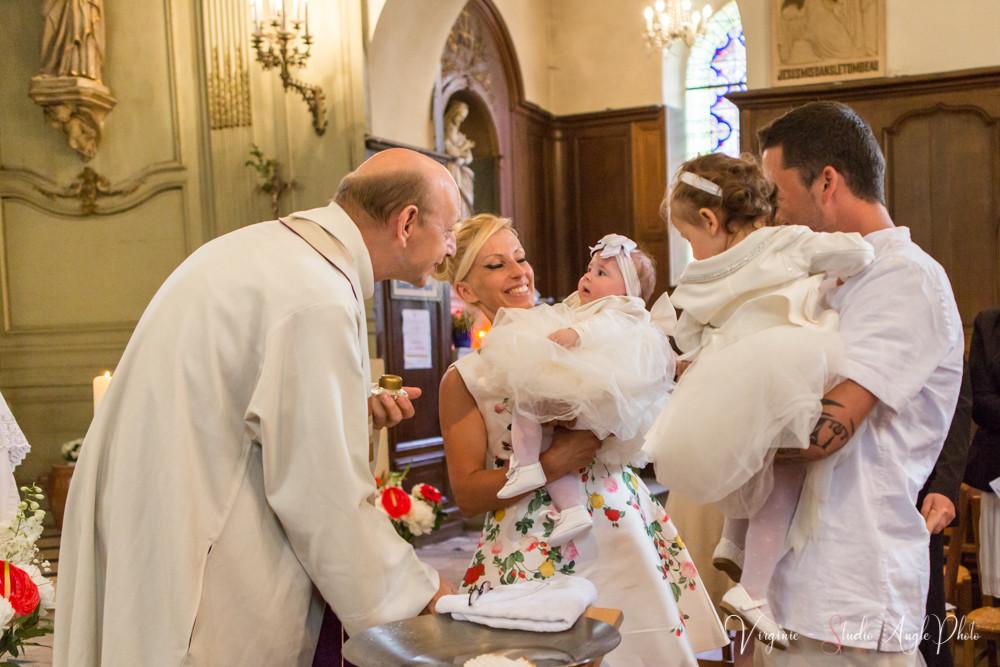 l'enfant regarde le pretre après avoir été baptisé