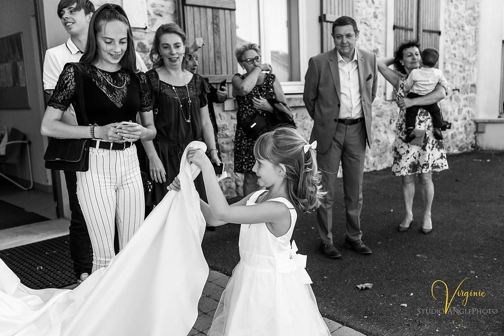 jeune fille tient la traîne de la robe de mariée