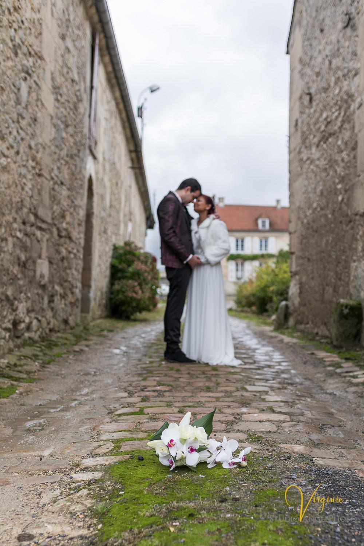 moment de tendresse entre les mariés avec le bouquet au premier plan