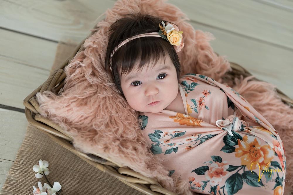bébé fille emmaillotée dans un wrap fleuri