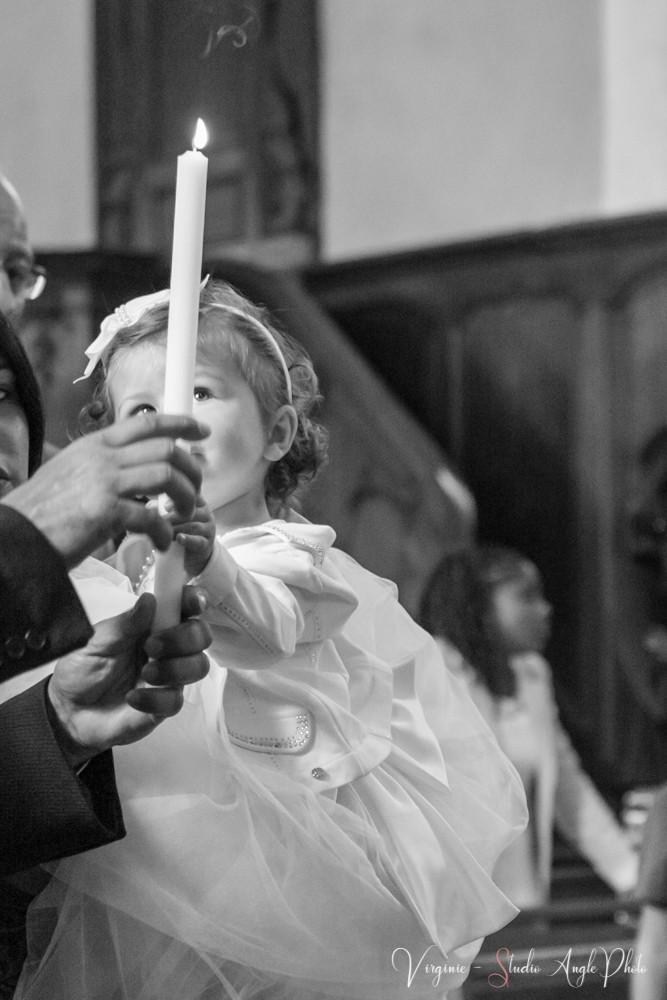 la petite fille regarde le cierge allumé tenu par son parrain