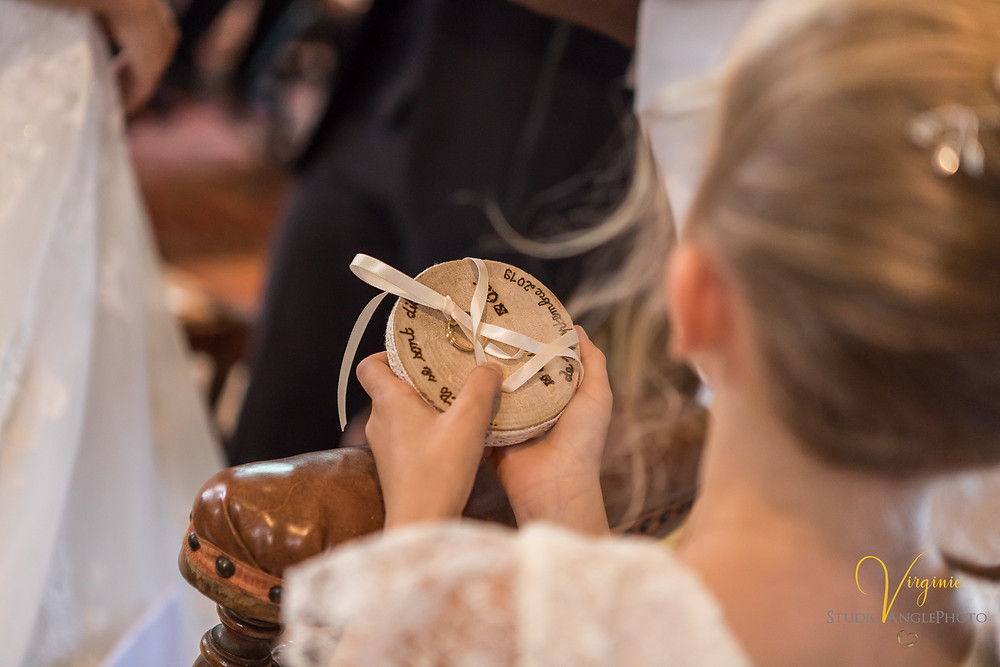 la fille des mariés tient les alliances dans ses mains à l'église