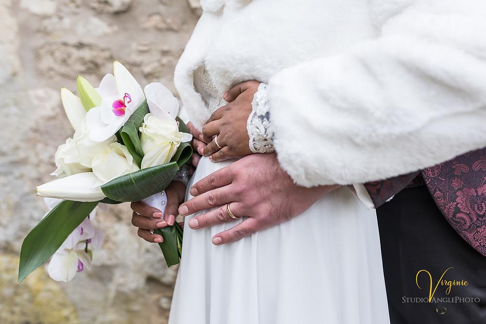 gros plan sur les alliances et le bouquet de la mariée