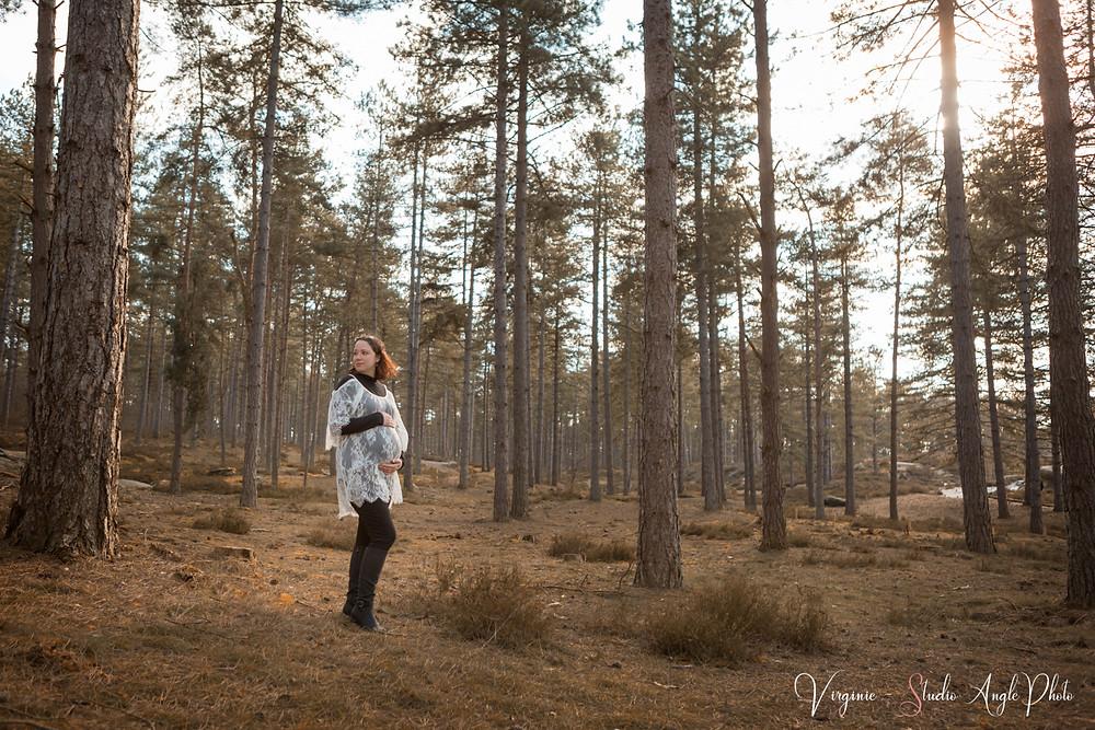 femme enceinte en forêt sous de grands arbres